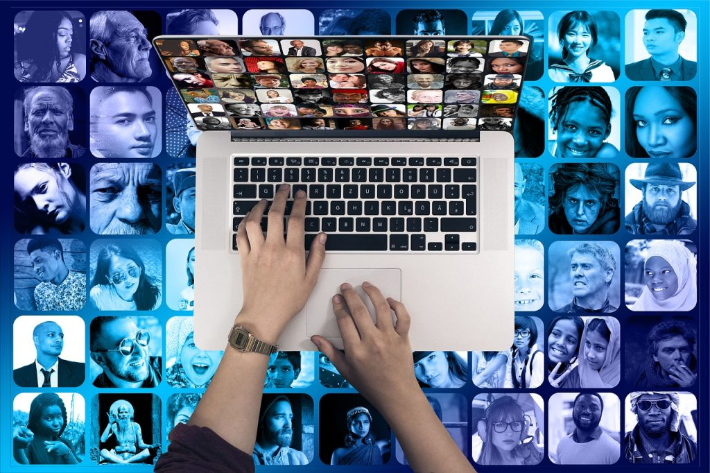 The hands of a user operate a keyboard. Mosaic background of faces from around the world